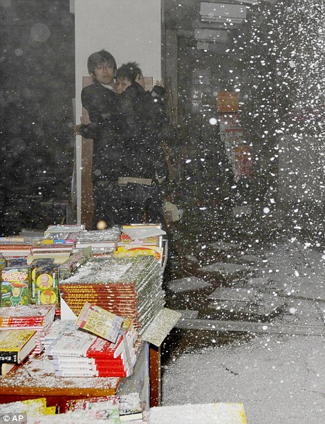 People at a book store react as the store's ceiling falls in Sendai, northern Japan Friday, March 11, 2011.