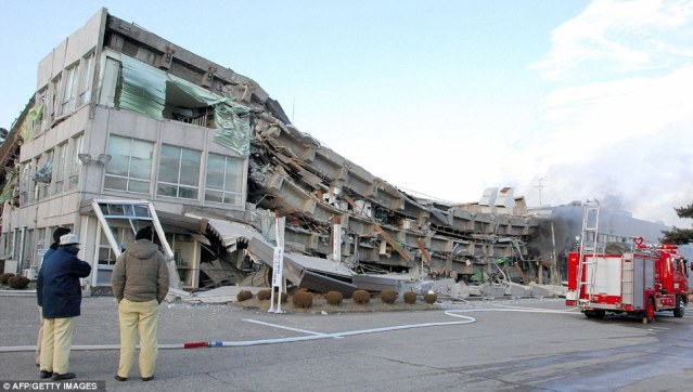 Collapsed: Three shocked workers look at the factory in Sukagawa city, Fukushima that only a short while earlier they had been working inside with dozens more unsuspecting colleagues