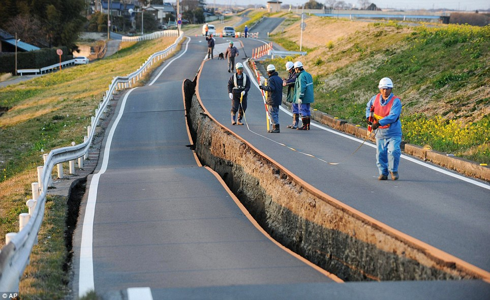 Caved in: In the aftermath of the biggest earthquake in Japan's history, workers survey the huge hole in the middle of a road in Satte