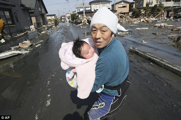 ... And fear: Upon hearing another tsunami warning, a father tries to flee to safety with the baby girl he has just been reunited with