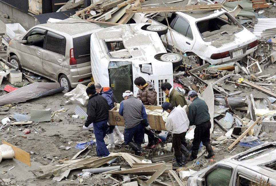 People carry the body of a victim through debris in Kesennuma, Miyagi, northern Japan