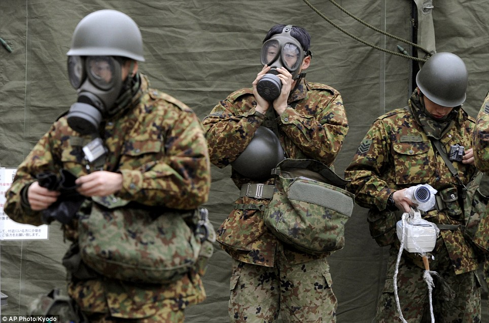 Clean up: Japanese soldiers prepare to wash away radioactive material emitted by the in the stricken reactor