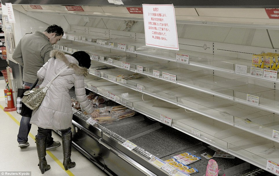 Panic buying: People shop for food from an almost empty shelf at a store in Tokyo