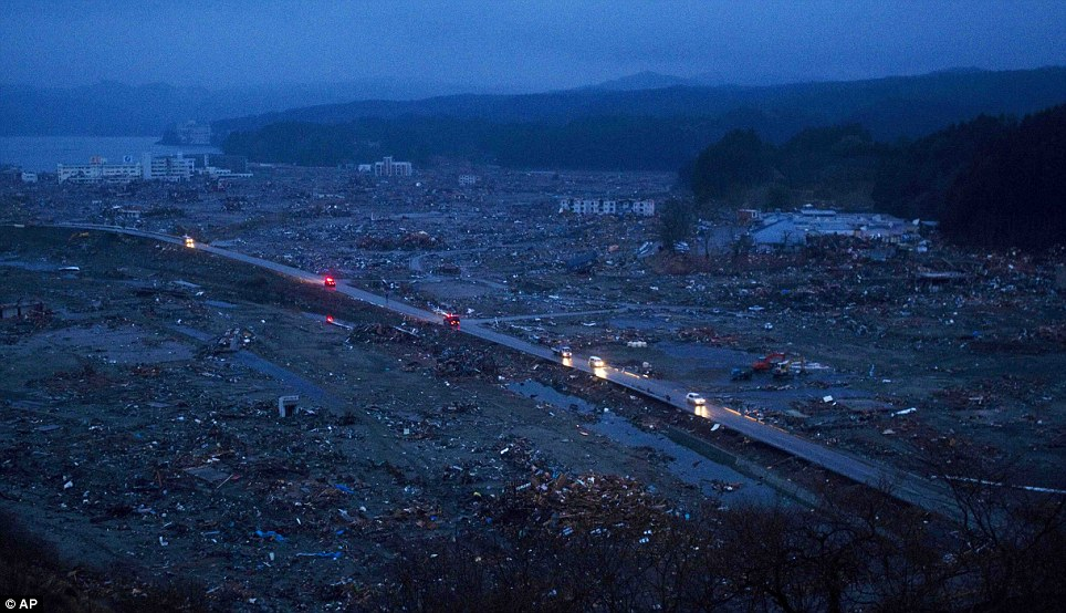 Eerie: Cars drive along one of the few passable roads in the devastated Minamisanriku where 10,000 people are feared dead