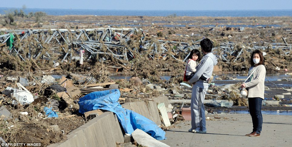 Cut adrift: Local residents look at debris brought by the huge tsunami in Minamisoma, before the exclusion zone was brought in