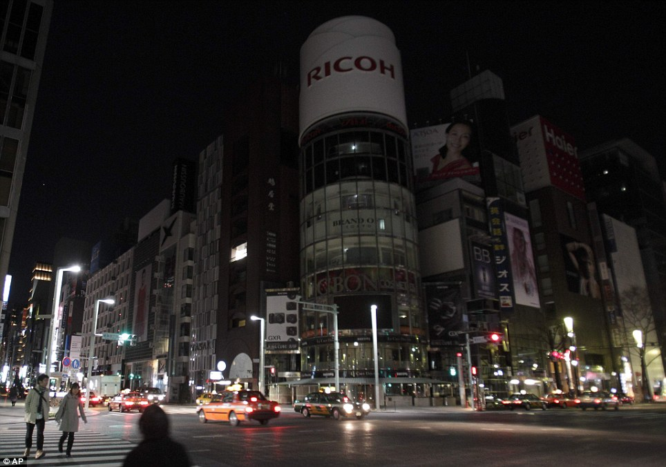 Ghost town: A landmark crossroads in Tokyo's Ginza district is eerily dark and empty as citizens stay indoors after warnings about a radioactive cloud from the stricken nuclear plant 150 miles away