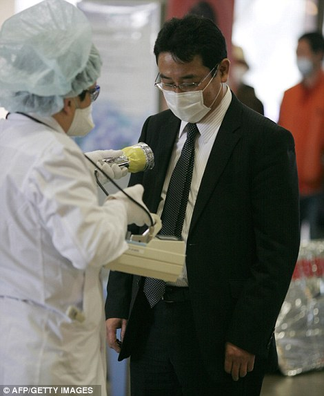 A businessman receives a radiation scan at a screening centre in Koriyama