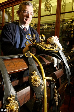 State Harness Cleaner David Oates cleans the Round Buckle, part of the State Harness, at the Royal Mews in central London