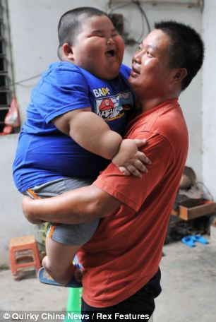 Heavy weight: Lu Hao with his father Lu Yuncheng, who breaks into a sweat just holding his son