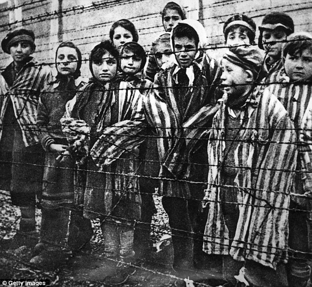 Victims: Children behind a barbed wire fence at at Auschwitz, where Mengele killed up to 400,000