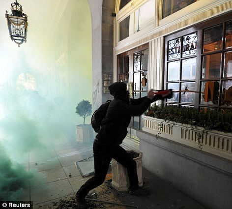 Chaos: A protester smashing windows at The Ritz in London