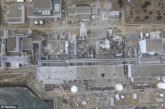 Too dangerous: This aerial photograph of the Fukushima plant shows the damaged reactors three and four at the which will now be entombed in concrete after the battle to contain radiation was lost