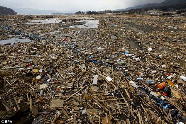 Desolation: Wood, fishing equipment and other debris floats on a river in Ofunato