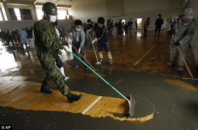 Mopping up: Ground Self-Defense Force soldier removes mud from a high school gymnasium in Ishinomaki