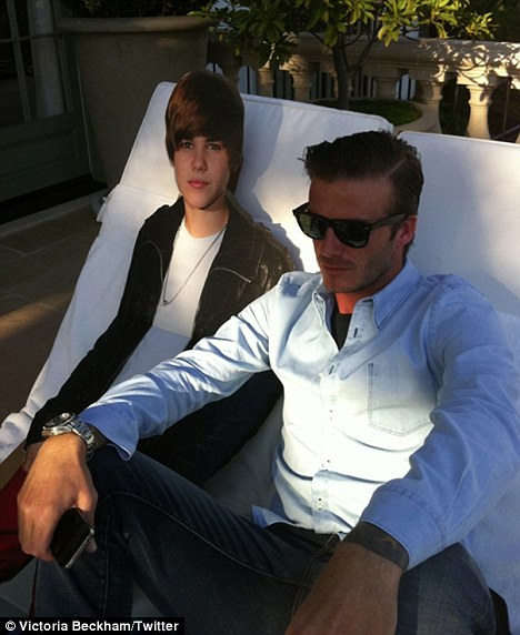 Spot the cut-out: Victoria Beckham posted a photo of husband David sat beside a cardboard cut-out of Justin Bieber