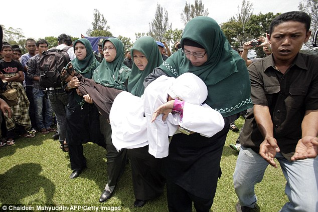 Sharia Officials carry Mukhtar who collapsed after the caning to a local hospital