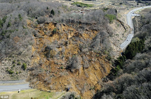 Landslide: Mud and trees cover part of a road in Iwaki after a landslide caused by a magnitude 7 earthquake yesterday