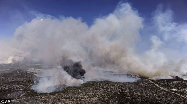 Smoke rises in the air as wildfire in Coke County, Texas, burns yesterday across the southern American state