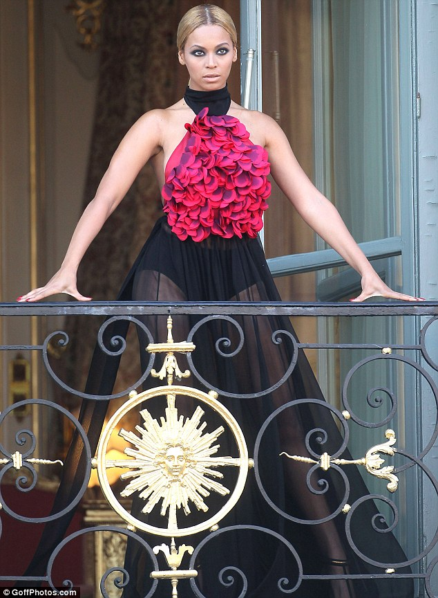 Vision: Beyonce appears on the balcony at the Ritz Hotel in Paris yesterday where she was taking part in a photoshoot for Harper's Bazaar magazine