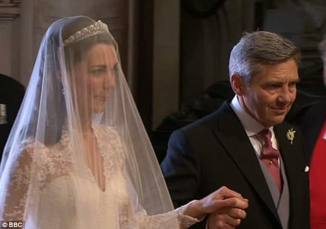 Brilliant in white: Kate Middleton is taken up the aisle by her proud father Michael