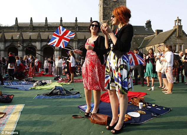 Revelry: Royal fans stand together during a special breakfast at St Andrews university. Revellers will watch proceedings as they unfold in London on large monitors dotted around the quadrangle.