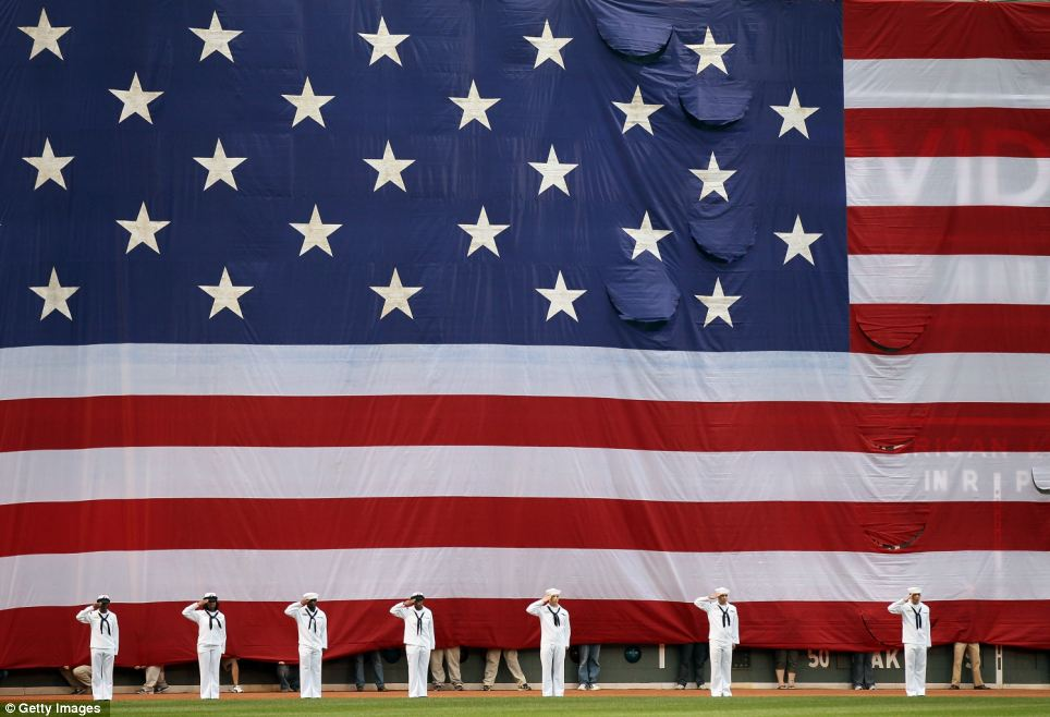 A giant flag is unveiled at Fenway Park as the national anthem is played before the game between the Boston Red Sox and the Los Angeles Angels