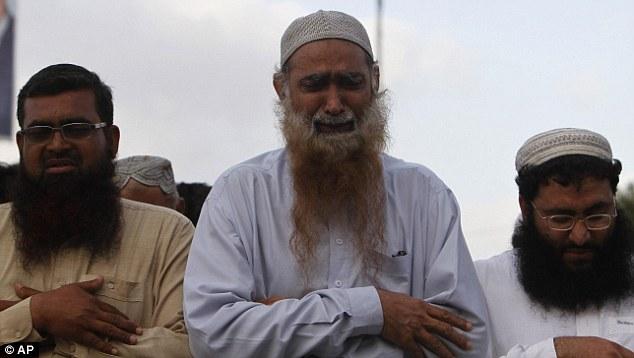 Tears for a terrorist: Supporters of Pakistan's religious party Jamatut Dawa offer funeral prayers for Osama Bin Laden in Karachi, Pakistan