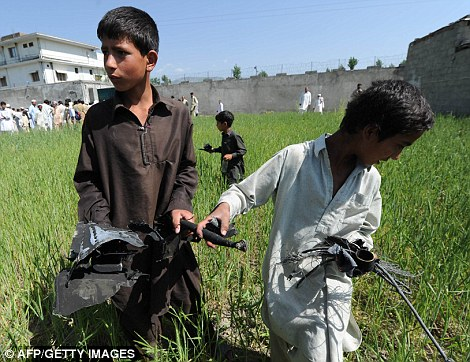 Two Pakistani boys collect pieces of the wrecked chopper which was burnt by special forces