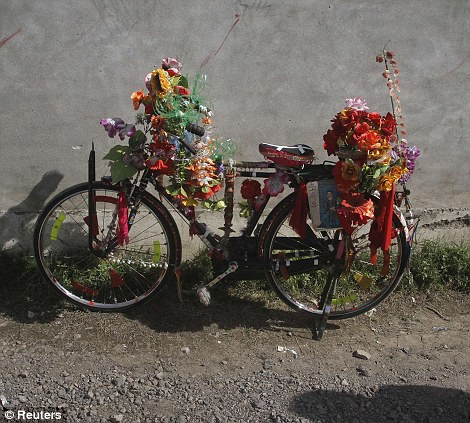 Is this Bin Laden's bike? A resident has decorated a bicycle outside the terrorist's compound with flowers after he was shot