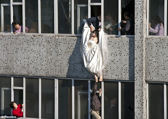 Desperate: The unidentified bride-to-be hangs from a seventh-storey window