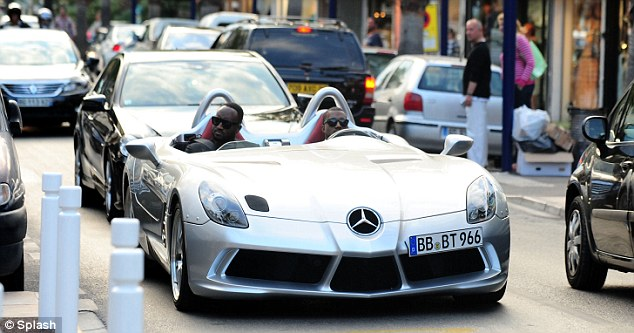 Ruling the road: Kanye makes every effort to arrive in style as he drives the sought after sport scar to Elton John's charity benefit in honor of the late Elizabeth Taylor