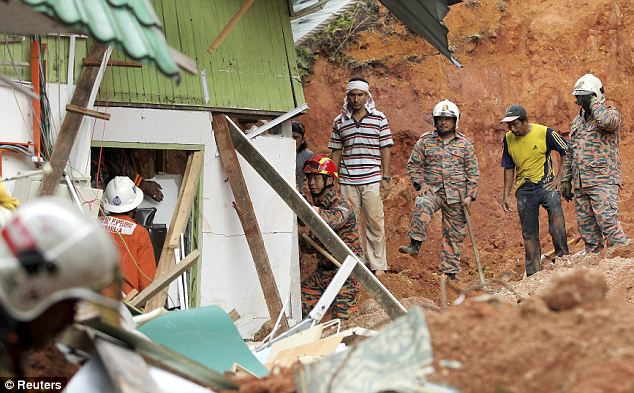 Rescuers pause to insect the building before they carry on. The orphanage house was half buried by the landslide