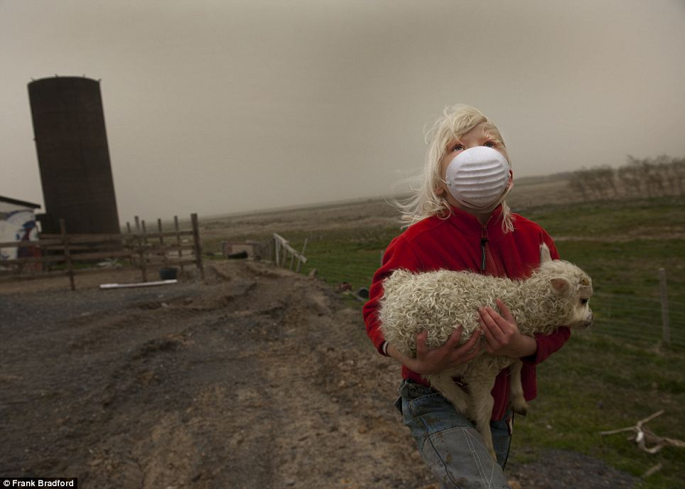 Looking up to the darkened sky because of the ash cloud, Sunna Agustdottir, seven, carries a new-born lamb to shelter at the family farm in Longumyri, Iceland