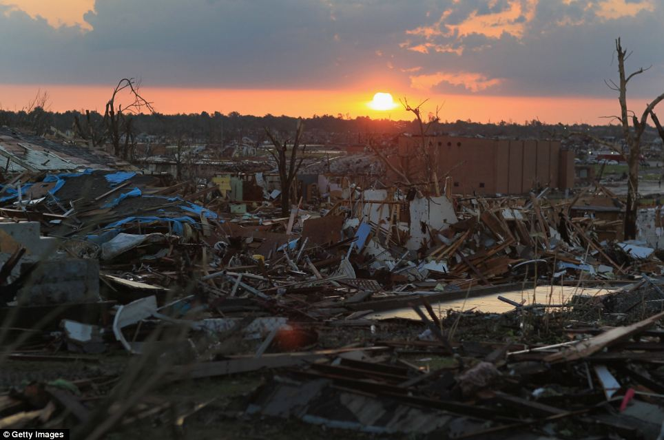 New dawn: The sun rises over devastated Joplin on Tuesday as the search for survivors continues