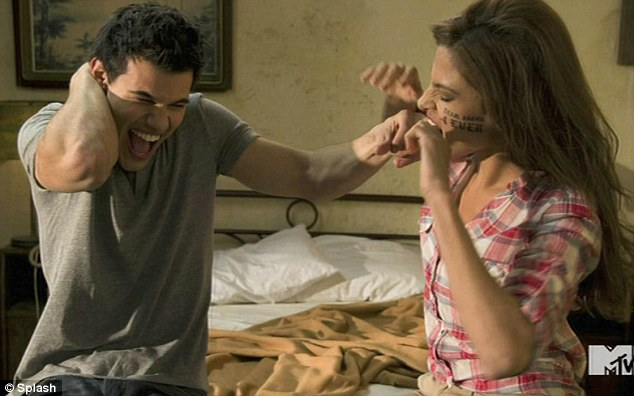 Gag-laden: In the clip she gets a tattoo on her face and also bites off Taylor Lautner's finger