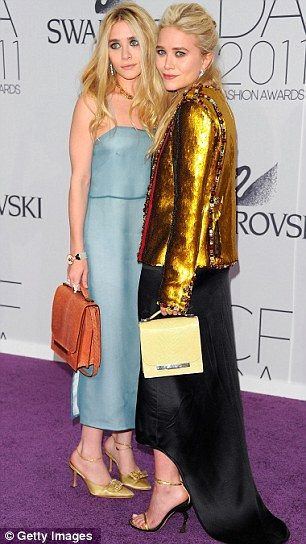 Double style: Ashley (L) and Mary-Kate Olsen (R) arrive in contrasting outfits with Ashley in a blue pastel gown and Mary-Kate wearing a brassy fold jacket and black skirt