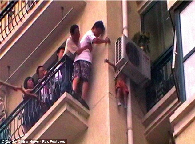 Terror on the eighth floor: Rescuers prepare to grab the three-year-old boy as he begins to slip after becoming wedged in an air conditioner