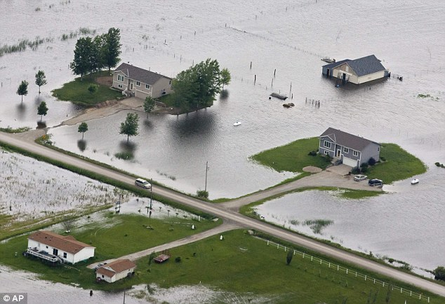 Disaster: Flood waters from the Missouri River engulf homes in neighbouring Iowa. More than 250 residents have now been evacuated from Missouri after levees broke