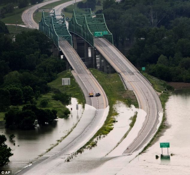 Stranded: Cars stop hopelessly, stranded by floodwaters over a bridge