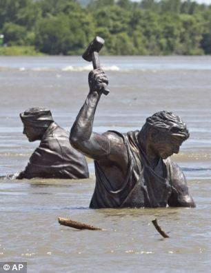 Deluge: Statues of workers, part of Monument for Labor by Matthew J. Placzek, stand in the rising waters of the Missouri River, in Omaha