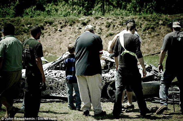A closer look: Shooters gather around the car to admire their handy work