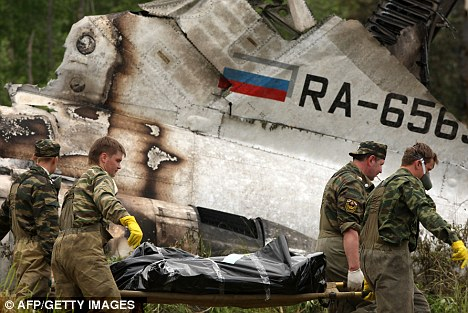 Recovery: Rescuers carry the body of a passenger past the wreckage of the Tu-134 plane on Tuesday