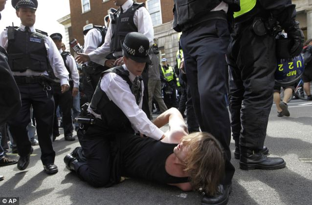 A police officer holds down a protester in Whitehall during the one-day strike