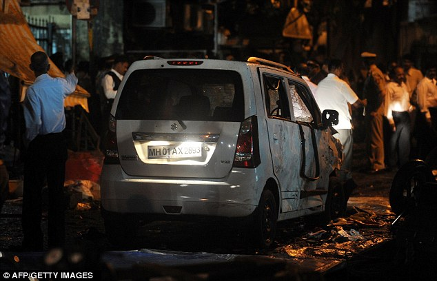 Debris: Indian security officials gather around a damaged vehicle at a blast site at the Opera House