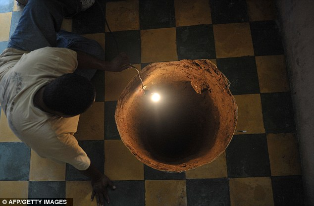 Wake up call: A female resident of Guatemala City awoke this morning to find this 40ft sinkhole had formed under her bed as she slept