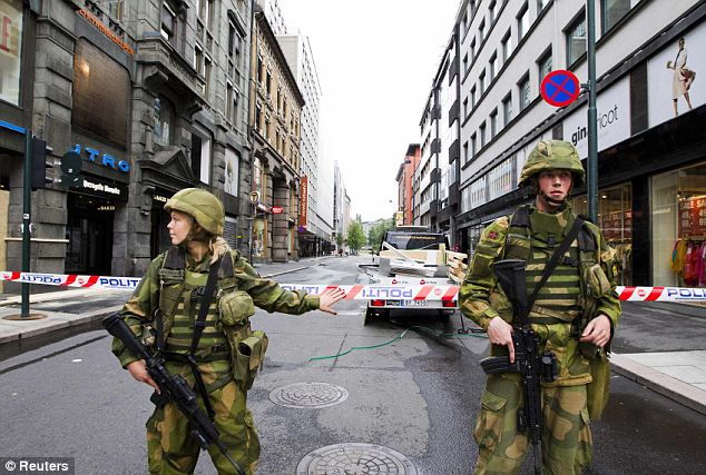 Soldiers guard a cordoned off area in central Oslo the day after the massive blast which killed seven people