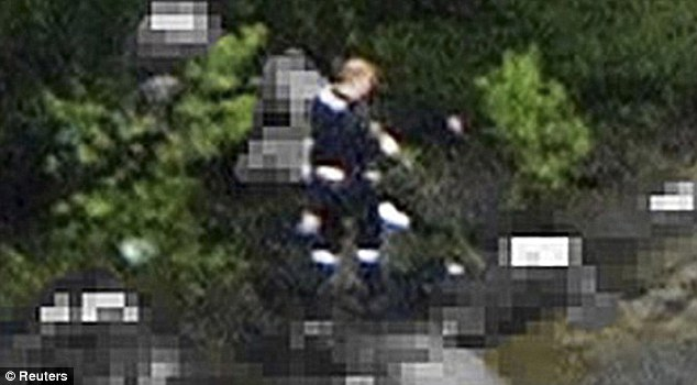 Rampage: This picture, taken from a helicopter, shows Anders Behring Breivik walking with a gun in hand among bodies on Utoya