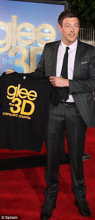 Suited and booted: Cory Monteith, who plays Finn Hudson, can't keep a straight face for long and poses with merchandise