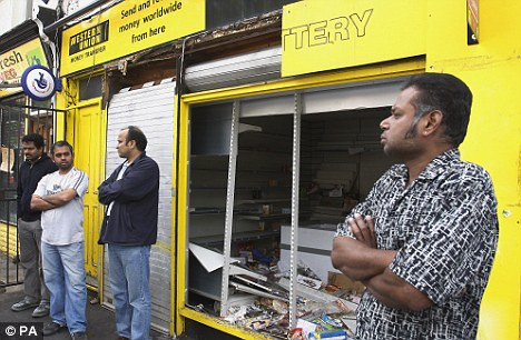 Protection: Asian shopkeepers stand outside their store in Hackney that was battered by the looters. This time, though, they're ready to take them on