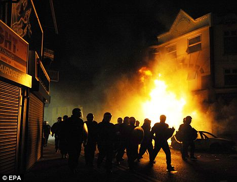 Street wars: Riot police patrol streets lined with burning building in Croydon during the riots there. It is likely that Laura Foley's sister was on duty